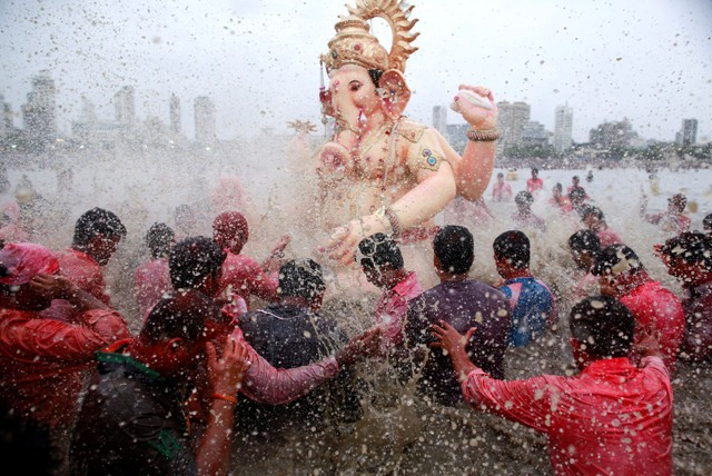 Devotees splash water on an idol of Hindu elephant god Ganesh, the deity of prosperity, as it is carried for immersion into the Arabian Sea on the last day of the Ganesh Chaturthi festival in Mumbai September 8, 2014. Ganesh idols are taken through the streets in a procession accompanied by dancing and singing, and later immersed in a river or the sea, symbolising a ritual seeing-off of his journey towards his abode, taking away with him the misfortunes of all mankind. REUTERS/Danish Siddiqui (INDIA - Tags: RELIGION SOCIETY TPX IMAGES OF THE DAY) - RTR45E4R